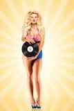 Bikini and vinyl. Beautiful pinup bikini model, holding an LP vinyl record on colorful abstract cartoon style background stock image