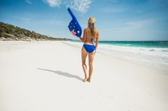 Bikini woman with large pointing finger on the beach in Australia. Bikini woman holding a large blow up pointing finger with Australian flag stands on a beach in stock photos