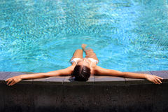 Bikini woman lying relaxing in infinity pool. At luxury resort spa retreat. Beautiful unrecognizable woman sunbathing in swimsuit on the edge of pool enjoying royalty free stock photos