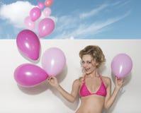 Bikini woman with pink balloons Stock Photos