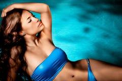 Bikini woman by the pool. Beautiful brunette in blue bikini enjoy by the pool Royalty Free Stock Photo