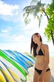 Bikini woman renting surfboard in Waikiki beach. Bikini beach woman at surfboard rental surf shop. Happy Asian girl walking next to rack of many surf boards to Royalty Free Stock Photos