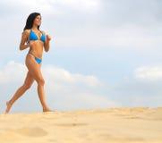 Bikini woman running on sand stock photo