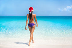 Bikini woman in santa hat on tropical beach. For Christmas vacation travel stock image