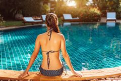 Bikini woman sexy in pool relaxing rear view. Resting in vacation on summer season with hat at resort swimming pool edge stock images