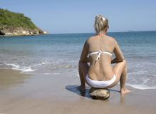 Bikini woman sitting coconut tropical beach Royalty Free Stock Photography