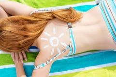Bikini Woman With Sun Drawn On Back At Beach. Top view of a young woman resting in bikini with sun drawn on back at beach Stock Photos