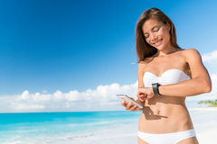 Bikini woman using smart phone syncing watch data Royalty Free Stock Photo