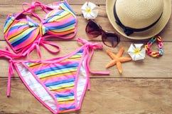 Bikini y accesorios coloridos de la belleza en el piso de madera para el viaje Imagenes de archivo