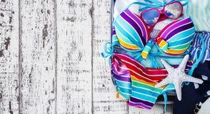 Bikini y ropa coloridos en equipaje en el fondo de madera fotos de archivo