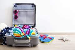 Bikini y ropa coloridos en equipaje en el piso laminado fotografía de archivo libre de regalías