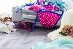 Bikini y ropa coloridos en equipaje en la cama imagen de archivo