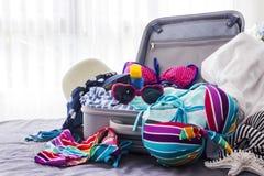 Bikini y ropa coloridos en equipaje en la cama fotos de archivo libres de regalías