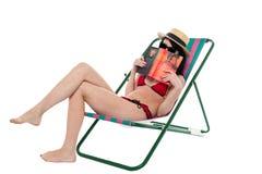 Bikinidam som döljer hennes framsida med en bok Arkivfoton