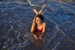 Bikiniflickan kopplade av att ligga på strandsanden royaltyfria bilder