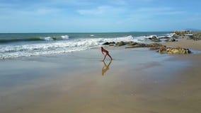 Bikiniflickan står i yoga poserar på stranden på stenar lager videofilmer