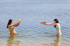 bikiniflickatrycksprutor play vatten två Royaltyfri Bild