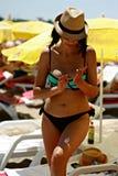 Bikinikvinna som applicerar Sunscreen på stranden Royaltyfri Foto