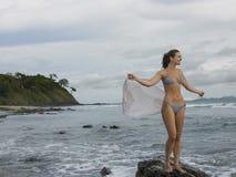 Bikinikvinnaanseendet vaggar på på stranden Arkivfoton