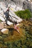 Bikinikvinnasammanträde vaggar på i dammet royaltyfri fotografi