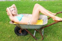 Bikinimädchen in einer Schubkarre. Lizenzfreie Stockbilder