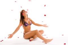 Bikinimädchen mit den rosafarbenen Blumenblättern stockfotografie