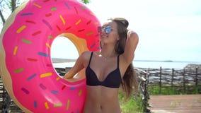 Bikinimeisje die met bestrooide doughnutvlotter bij pool in zondag lopen Partij, hotel, strand, vakantie, vakantie, reis stock videobeelden