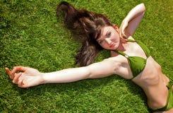 bikinin gräs ner den liggande modellen royaltyfria foton