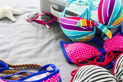 Bikinis and clothes in luggage on the bed royalty free stock photography