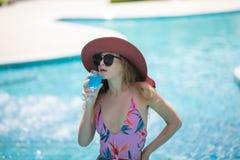 Bikinis de la ropa de mujer y cócteles de consumición en el verano caliente en la piscina fotografía de archivo