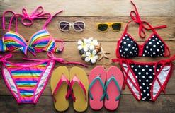 Bikinis, sunglasses, shoes, two sets placed on a wooden floor. Bikinis, sunglasses, shoes, two sets placed on a wooden floor royalty free stock image