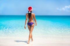 Bikinivrouw in santahoed op tropisch strand stock afbeelding