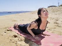 Bikram yoga bhujangasana pose. Yoga teacher practising at the beach pose bhujangasana Royalty Free Stock Image