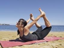 Bikram yoga dhanurasana pose. Yoga teacher practising at the beach pose dhanurasana Stock Photo