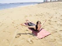 Bikram yoga paorna salabhasana pose. Yoga teacher practising at the beach pose paorna salabhasana Stock Image