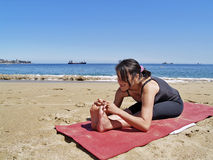 Bikram yoga paschimottanasana pose at beach. Yoga teacher practising at the beach paschimottanasana Royalty Free Stock Photos