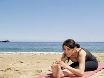 Bikram yoga sit-up pose at beach. Yoga teacher practising at the beach pose sit-up Stock Image