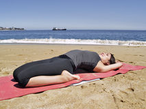 Bikram yoga supta bajrasana pose at beach Royalty Free Stock Images