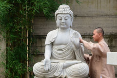 Biksu membersihkan patung菩萨bersih pada Hari Waisak 库存照片