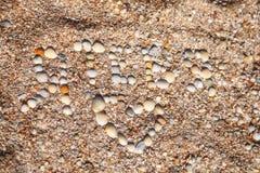 Bikt av förälskelse som göras av skal, strand med skal royaltyfria foton