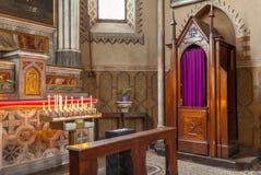 Biktstol och altare med stearinljus i kyrkan Arkivfoton