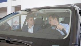 Bilåterförsäljare, råder säljaren klienten i den nya maskinen, auto affär arkivfilmer