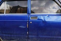 Bil av den ryska tillverkningen efter en krasch med bucklaskrapor och defekter av kroppsdelen fotografering för bildbyråer