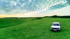 Bil för bonde` s och grönt fält mot himlen Rysk lantlig liggande royaltyfria bilder