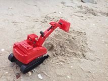 Bil för grävskopa för leksak för barn` s röd på sand, industriella symboler Royaltyfria Bilder