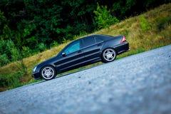 Bil för Sedanlyxsvart som parkeras i parkeringsplatsen nära en skog Arkivbilder