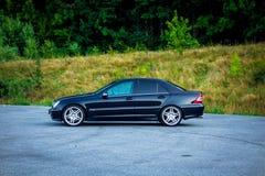 Bil för Sedanlyxsvart som parkeras i parkeringsplatsen nära en skog Royaltyfria Foton