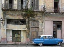 Bil för tappningamerikanblått som parkeras utanför ett herrelöst gods som bulling i havannacigarr, Kuba Royaltyfri Foto