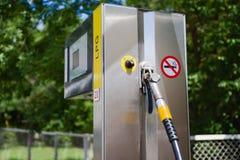 Bil i bensinstation Tanka, bensinutmataren, pumpen, handtag och pelare tanka estonia Tänt fönster av servicebutiken och c Arkivbilder