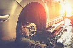 Bil i garage i för reparationsservice för auto mekaniker seminarium med den speciala maskinen som reparerar utrustning arkivfoto